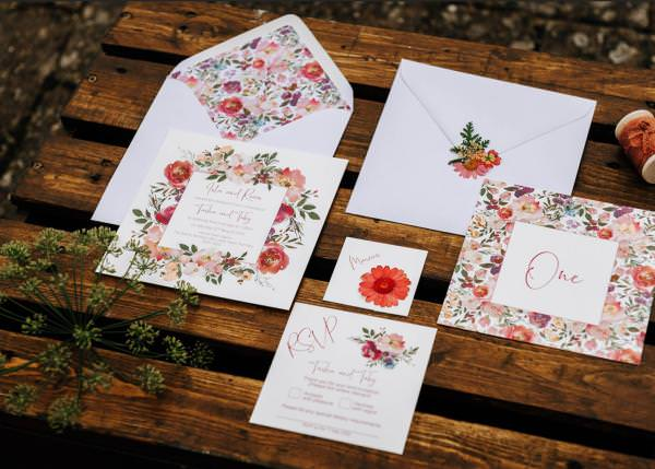 Bright floral wedding invitation in reds, coppers and orange hues